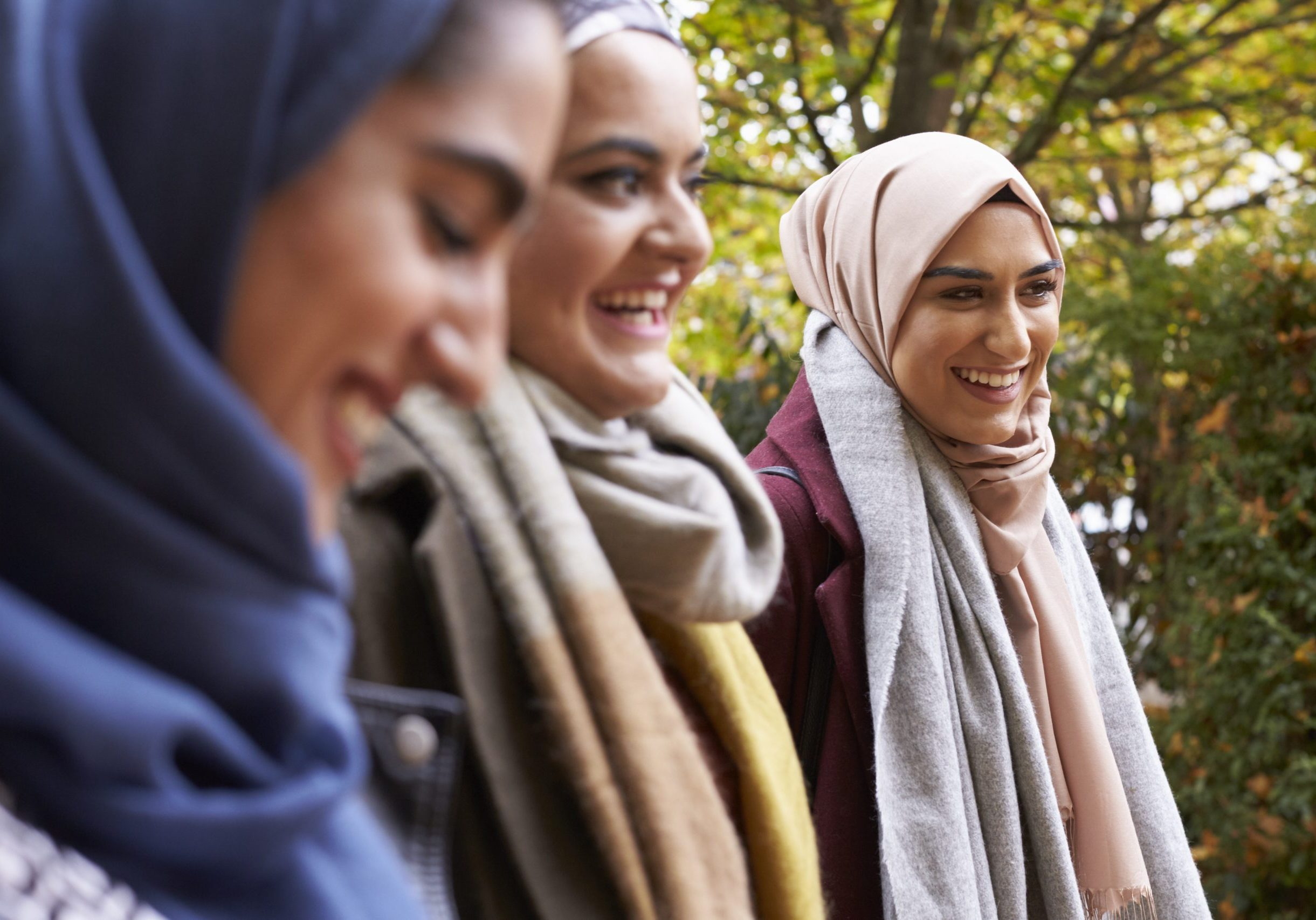 British Muslim Female Friends Meeting In Urban Environment